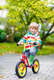 Scherzen Sie den Jungen, der draußen auf Fahrrad am regnerischen Tag fährt Lizenzfreies Stockfoto