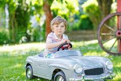 Scherzen Sie den Jungen, der draußen mit großem Spielzeugauto fährt Stockbilder