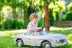 Scherzen Sie den Jungen, der draußen mit großem Spielzeugauto fährt Stockfoto
