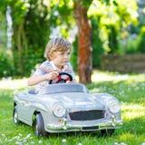 Scherzen Sie den Jungen, der draußen mit großem Spielzeugauto fährt Lizenzfreie Stockfotografie