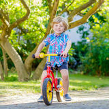 Scherzen Sie den Jungen, der Dreirad oder Fahrrad im Garten fährt Stockbilder