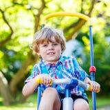 Scherzen Sie den Jungen, der Dreirad oder Fahrrad im Garten fährt Stockfotos
