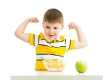 Scherzen Sie den Jungen, der gesunde Nahrung isst und seine Stärke zeigt Lizenzfreies Stockbild