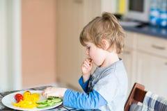 Scherzen Sie den Jungen, der gesundes Lebensmittel im Kindergarten oder zu Hause isst lizenzfreie stockfotografie