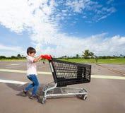 Scherzen Sie den Jungen, der leeren Warenkorb am Parkplatz drückt Lizenzfreie Stockfotos