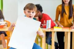 Scherzen Sie den Jungen, der leeres weißes Plakat mit Verschiedenartigkeit Freunden und te hält stockbilder