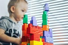 Scherzen Sie den Jungen, der mit Blöcken vom Spielzeugerbauer spielt Baby unfocused, Fokus auf Spielwaren lizenzfreie stockfotografie