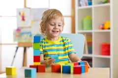 Scherzen Sie den Jungen, der mit Blockspielwaren in Kindertagesstätte spielt Stockfoto