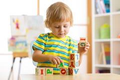 Scherzen Sie den Jungen, der mit Blockspielwaren spielt und Buchstaben lernt Lizenzfreie Stockfotos