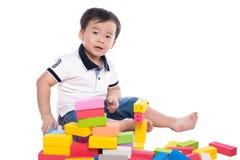 Scherzen Sie den Jungen, der mit Blockspielzeug über weißem Hintergrund spielt Lizenzfreies Stockbild