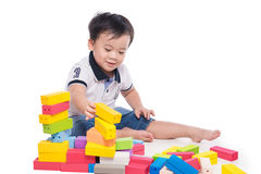 Scherzen Sie den Jungen, der mit Blockspielzeug über weißem Hintergrund spielt Stockfotos