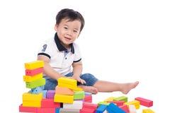 Scherzen Sie den Jungen, der mit Blockspielzeug über weißem Hintergrund spielt Stockfoto