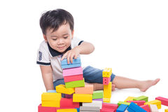 Scherzen Sie den Jungen, der mit Blockspielzeug über weißem Hintergrund spielt Lizenzfreie Stockfotos