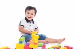 Scherzen Sie den Jungen, der mit Blockspielzeug über weißem Hintergrund spielt Lizenzfreie Stockfotografie