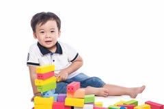 Scherzen Sie den Jungen, der mit Blockspielzeug über weißem Hintergrund spielt Lizenzfreies Stockfoto
