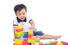 Scherzen Sie den Jungen, der mit Blockspielzeug über weißem Hintergrund spielt Stockbild