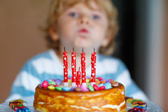 Scherzen Sie den Jungen, der seinen Geburtstag feiert und Kerzen auf Kuchen durchbrennt Stockbild