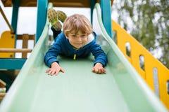 Scherzen Sie den Jungen, der Spaß hat und auf Spielplatz im Freien schiebt Stockbild