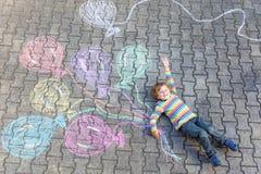 Scherzen Sie den Jungen, der Spaß mit den bunten Ballonen hat, die mit Kreiden zeichnen Stockbilder