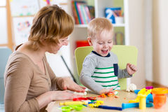 Scherzen Sie den Jungen und Mutter, die buntes Lehmspielzeug spielen Stockfoto