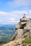 Scherzen Sie in der Kappe, die auf eine felsige Oberseite in den Bergen sitzt Lizenzfreie Stockfotografie