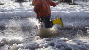 Scherzen Sie die Beine, die am Frühlingsnebenfluß mit schmelzendem Eis laufen stock video footage