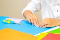 Scherzen Sie die Hände, die Grußkarte mit farbigem Papier am Tisch machen stockfoto