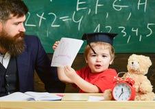 Scherzen Sie glückliche Studien einzeln mit Vater, zu Hause Einzelnes Schulungskonzept Kleiner Junge zeigt sein Schreibheft mit stockfoto