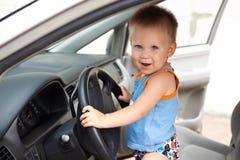 Scherzen Sie hinter dem Rad eines großen Autos Lizenzfreies Stockfoto