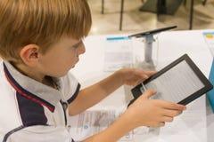 Scherzen Sie (8-9 Jahre) das Spielen mit Tablet-Computer in einem Shop stockbilder