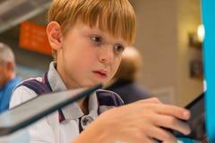 Scherzen Sie (8-9 Jahre) das Spielen mit Tablet-Computer in einem Shop stockfotos