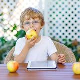 Scherzen Sie Jungen mit den Gläsern, die mit Tablette spielen und Apfel essen Lizenzfreie Stockbilder
