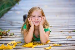 Scherzen Sie Mädchen in der Spätholzplattform mit den gelben Blättern im Freien Stockbild