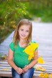 Scherzen Sie Mädchen in der Spätholzplattform mit den gelben Blättern im Freien Lizenzfreies Stockbild
