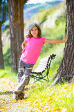 Scherzen Sie Mädchen mit Tarnungshosen und -kappe Parkbank in der im Freien Stockbilder