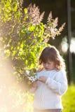 Scherzen Sie Mädchen nahe Baum mit Frühlingsblumen, Sonnenschein Lizenzfreie Stockfotos