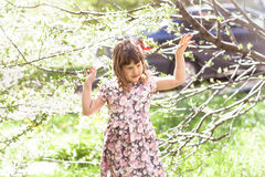 Scherzen Sie Mädchen nahe Baum mit Frühlingsblumen, Sonnenschein Stockfotografie