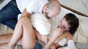 Scherzen Sie mit dem Vati, der zusammen Mutter auf Bett, die glückliche kitzelt Familie, die Spaßzeit hat stock footage