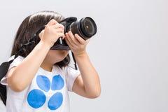Scherzen Sie mit Kamera auf Weiß/Kind unter Verwendung der Kamera/des Kindes unter Verwendung der Kamera DSLR, Atelieraufnahme Lizenzfreie Stockfotos
