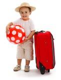 Scherzen Sie mit roter Kugel und dem Koffer, die zur Reise betriebsbereit ist Stockbilder