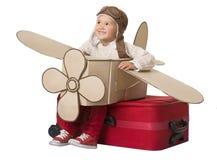 Scherzen Sie Reise auf Toy Airplane, das Kind, das im Urlaub Koffer sitzt stockfoto