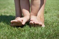 Scherzen Sie Stellung auf ihren Mutter ` s Beinen Stellung auf dem grünen Gras Lizenzfreie Stockfotografie