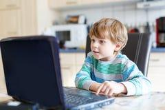 Scherzen Sie surfendes Internet des Jungen und das Spielen auf Computer Lizenzfreies Stockbild