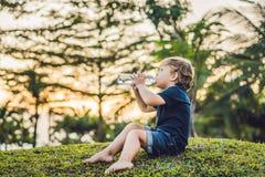 Scherzen Sie trinkendes reines Süßwasser in der Natur bei Sonnenuntergang Lizenzfreie Stockfotos