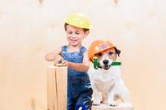 Scherzen Sie und sein Haustier an der Baustellefunktion als Erbauer Lizenzfreies Stockbild