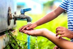 Scherzen Sie waschende Hände mit Mutter, Punkt des selektiven Fokus Stockbild