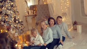 Scherzende Familie, die auf Baumhintergrund des neuen Jahres im gemütlichen Haus am Feiertagsvorabend aufwirft stock video footage