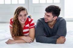 Scherzende kaukasische Liebe verbinden das Betrachten der Kamera in der neuen Wohnung Lizenzfreies Stockfoto