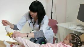 Scherzi alla ricezione di medico pediatrico, medico riceve i pazienti, bambino malato in ospedale, la clinica pediatrica, cardiog video d archivio
