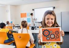 Scherzi in aula con la compressa che mostra i grafici dell'ingranaggio contro il fondo arancio Fotografia Stock